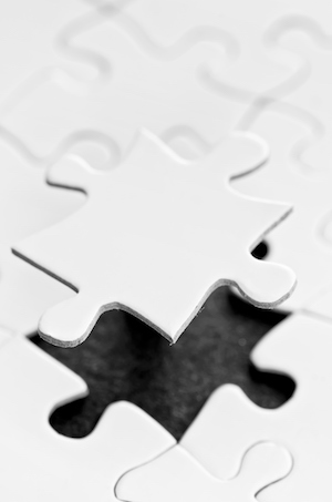 White puzzle pieces with one floating piece.